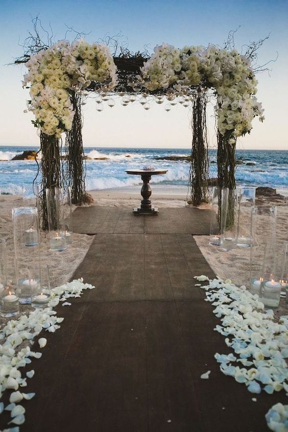 Arbor with roses and rose petals for a beach wedding