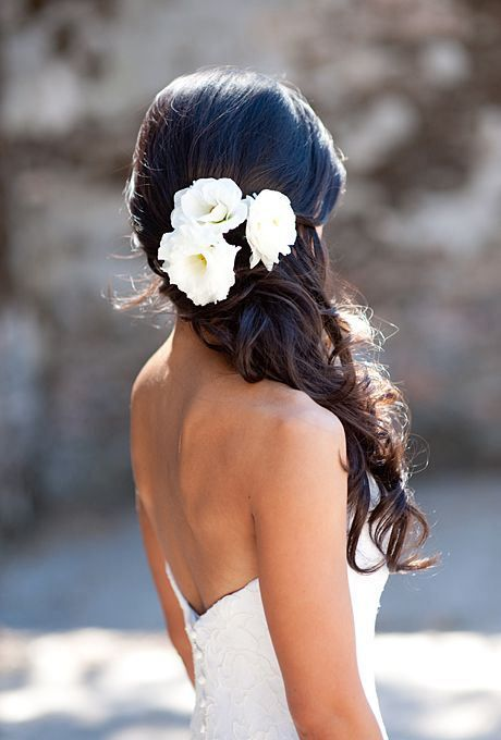 Beautiful hairdo with roses for a beach wedding look.