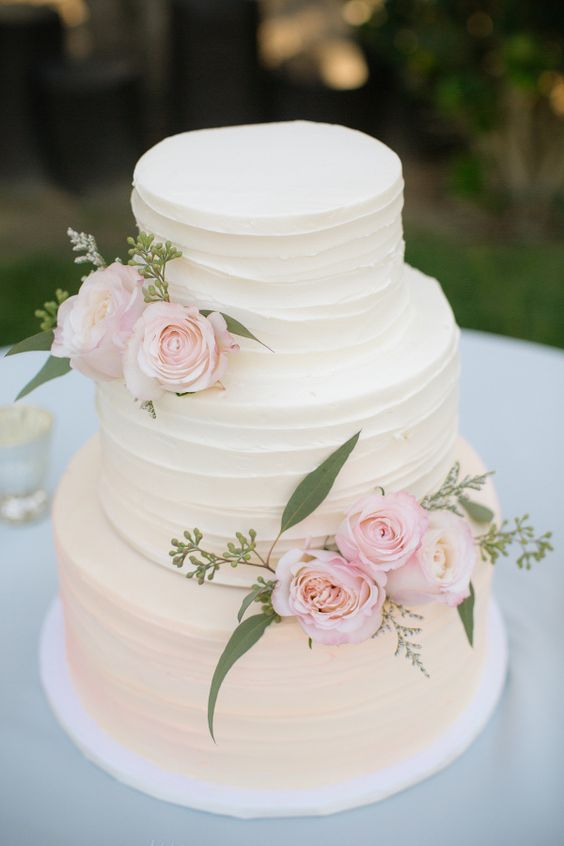 Iced wedding cake with roses. Would fit well with a beach wedding.