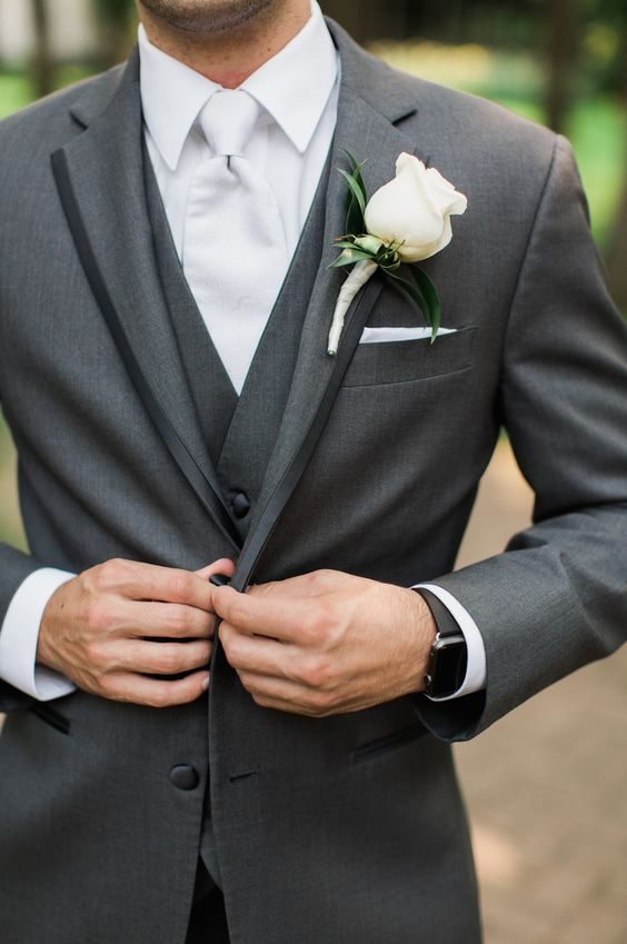white wedding. Groom with rose.