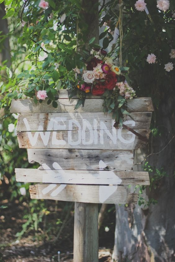 Perfect wedding entrance sign with flowers and roses for a bohemian wedding.