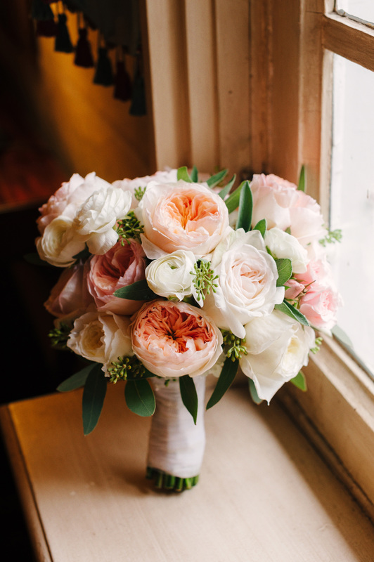Bouquet in cream, pink and peach with David Austin roses, ranunculus & seeded eucalyptus.