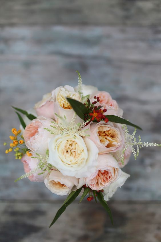 The soft pink outer petals and old gold center petals of Edith wedding roses reflect the perfect melding of color tones between peach Juliet and buttermilk Patience in this bridesmaid bouquet.