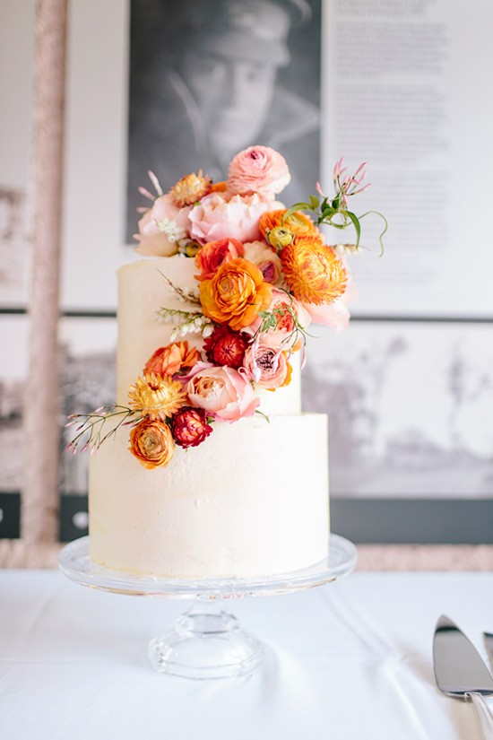 Simply beautiful two tier cake with fresh roses, everlasting daisies, ranunculus buds, jasmine and lily of the valley int tones of orange, pinks and rich reds. The most beautiful combination for a Summer day.