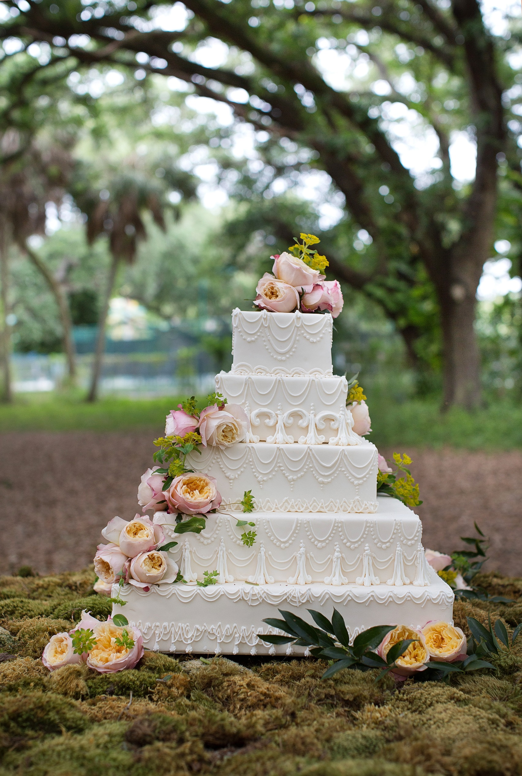 A majestic white five-layer wedding cake with gorgeous David Austin Edith roses.