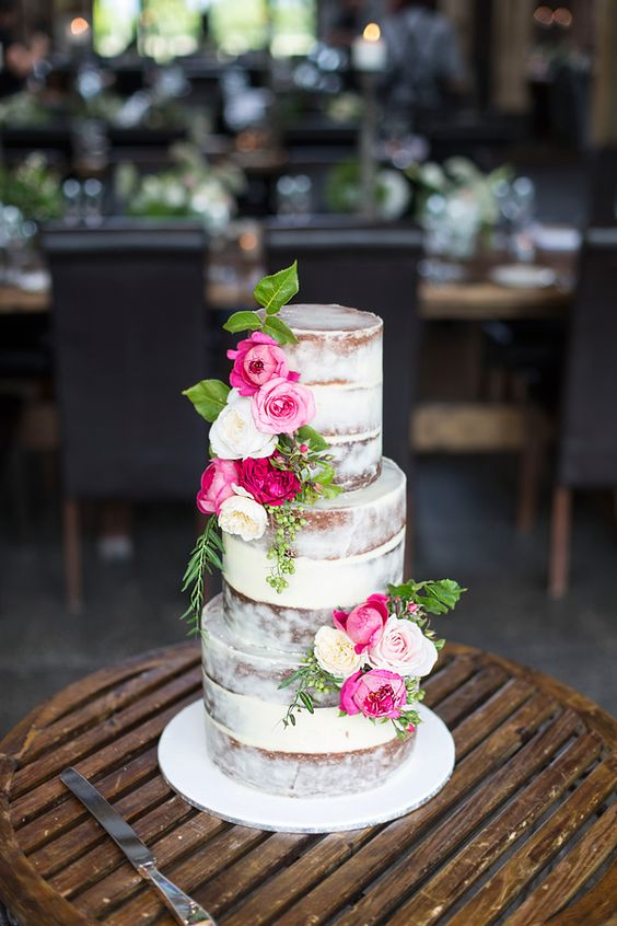 Semi naked wedding cake with bright pink florals.