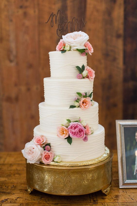 White wedding cake with piping and fresh roses.