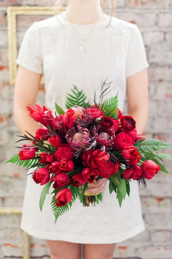 Daring combination of red roses and red tulips.