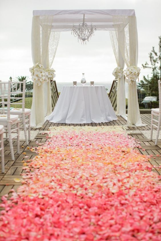 Going down the aisle on a carpet of rose petals with a coral ombre effect. How creative!
