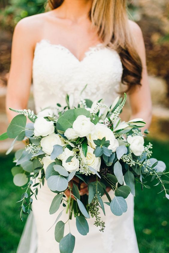 Lovely wedding bouquet with white David Austin Patience roses, cream garden roses, veronica, white ranunculus, olive branches, and a blend of different varieties of eucalyptus.
