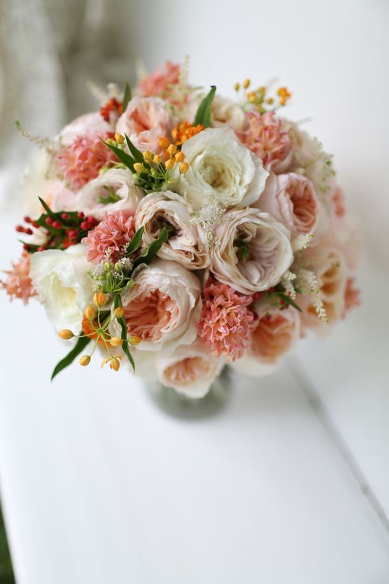 Stunning peachy-pink wedding bouquet with Juliet, Charity and Patience.
