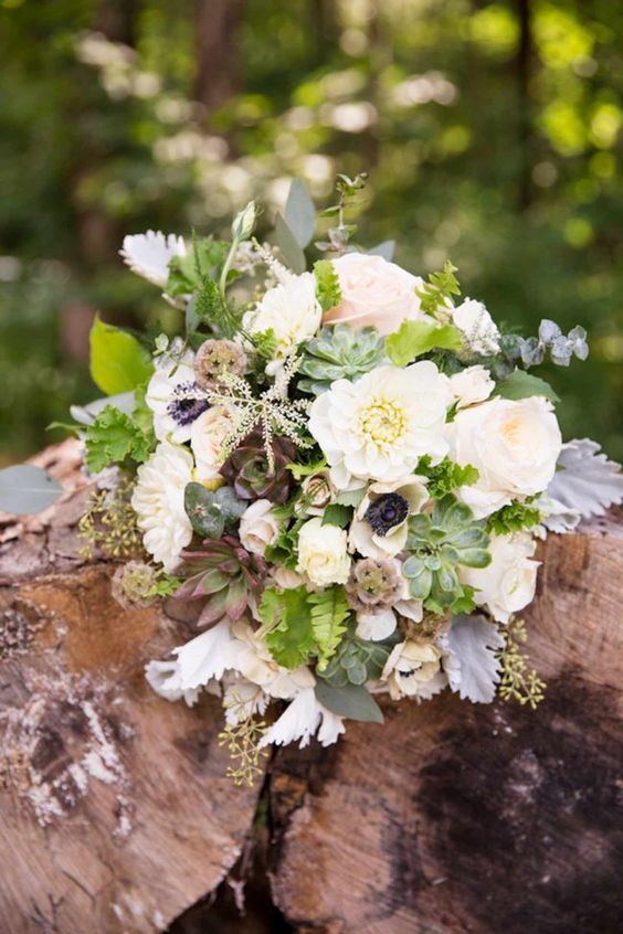 "Beautiful rustic Virginia mountain wedding bouquet with white anemones with black centers, the David Austin roses, ""Patience"", anemones with black eyes, white dahlias, porcelena spray roses and white O'Hara roses that were blush in the center. They were accented with foliage of dusty miller, scented geranium leaves and lily grass."