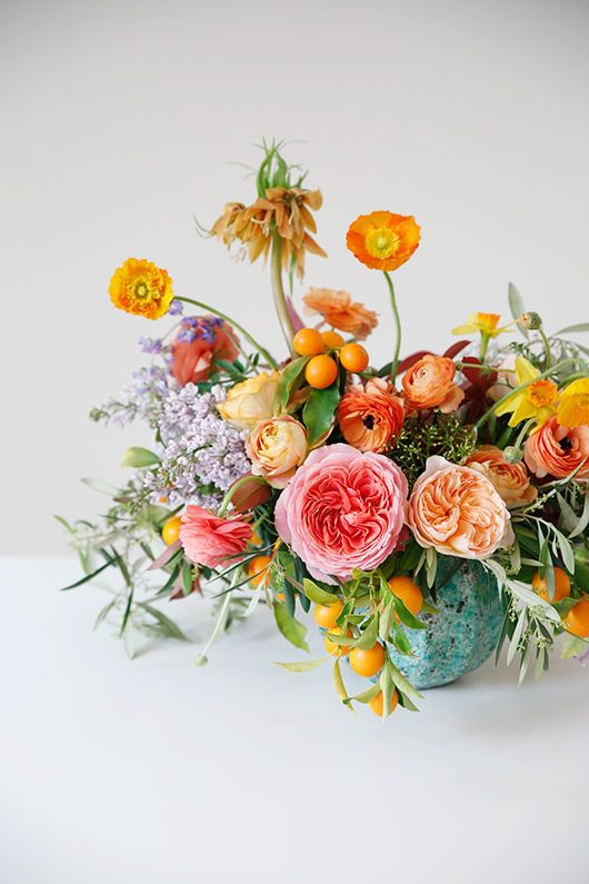 colorful arrangement of Romantic Antike garden roses, poppies, ranunculi, and kumquat branches. Perfect to get those spring vibes into your home.