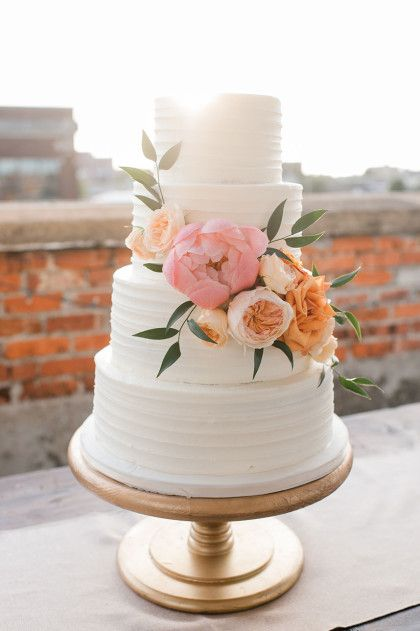 Elegant white piped cake with peonies and Juliet roses for a summer rooftop wedding.