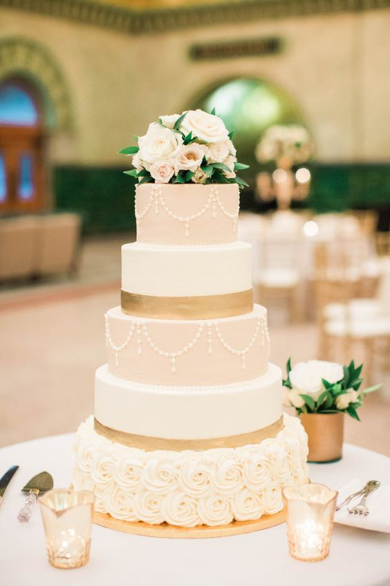 A sophisticated color palette with luxury details make up this stunning wedding cake.