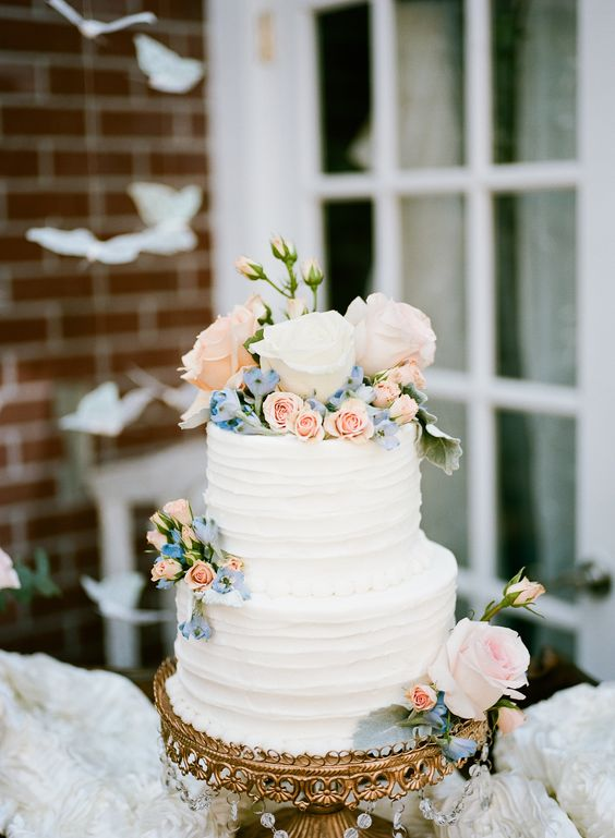 Buttercream wedding cake with blush a blue flowers.