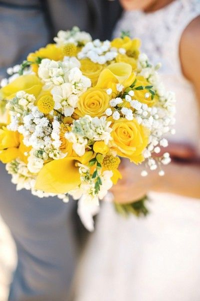 Yellow and white wedding bouquet with yellow roses, craspedia, calla lilies, stock, and baby's breath. Via Wedding Wire
