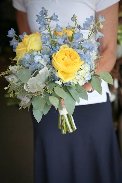 Blue and yellow wedding bouquet. Perfect for the bride or bridesmaid. Designed with blue hydrangea, yellow roses, light blue delphinium, dusty miller, and seeded eucalyptus. Via Backyard Garden Florist