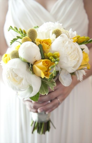 Summer wedding bouquet with yellow roses and white peonies.