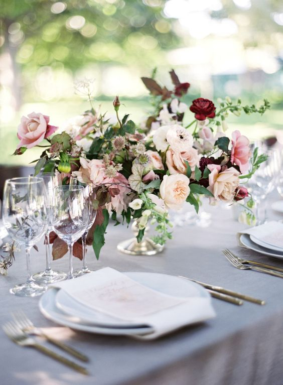 Elegant outdoor table setting with lush centerpieces. Via Style Me Pretty
