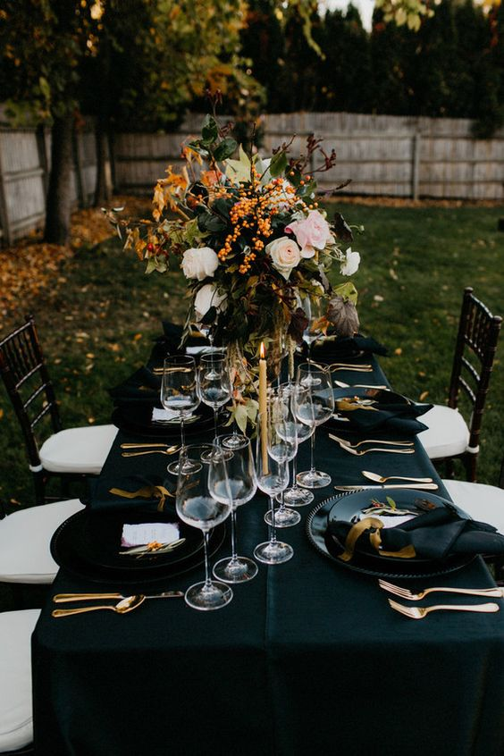 Dark fall table setting with over-sized florals and black linens. Via 100 Layer Cake