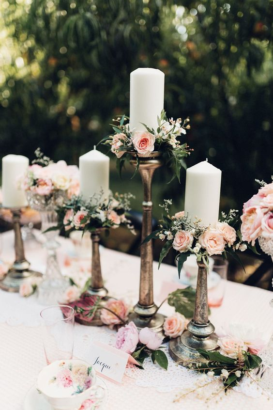 High candle holders with peach and pink garden roses that lift this outdoor wedding to another level. Via Rock My Wedding